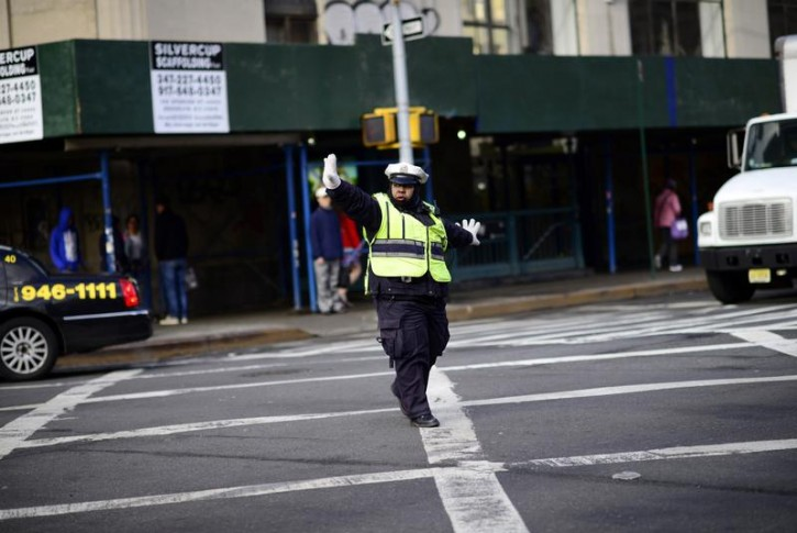 FILE - A police officer directs traffic during rush hour in downtown New York March 20, 2014. REUTERS/Dylan Martinez