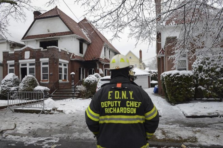 Firefighters stand near the site of a home fire in the Midwood neighborhood of Brooklyn, New York March 21, 2015. Reuters