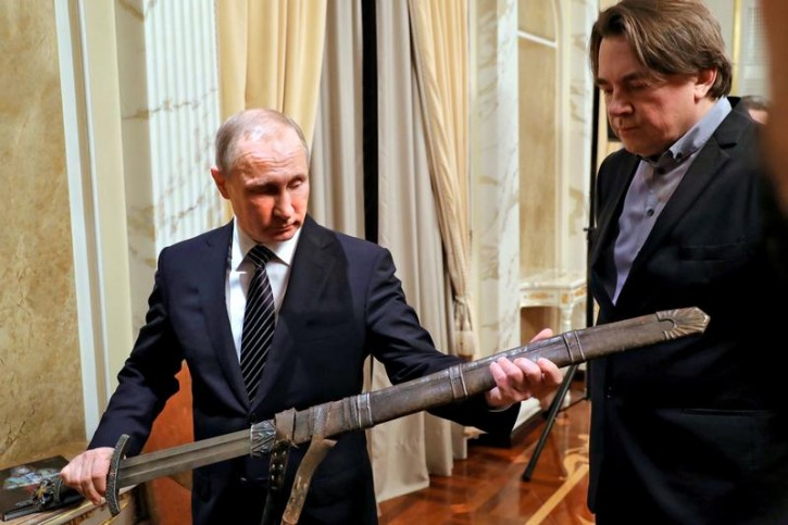 "Russia's President Vladimir Putin holds a sword during a meeting with the ""Viking"" film crew, as film producer and Director General of Channel One Russia Konstantin Ernst (R) looks on, in Moscow, Russia December 30, 2016.  Sputnik/Mikhail Klimentyev/Kremlin/via REUTERS"