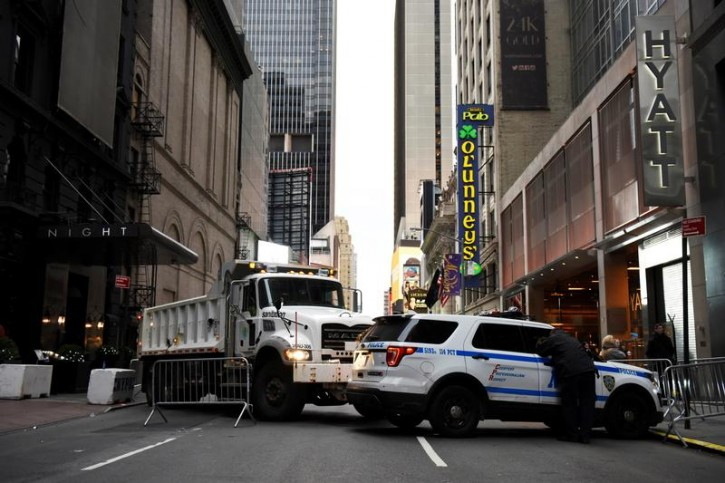 A dump truck filled with sand sits near a New York Police Department vehicle acting as a barricade near New Year's Eve festivities in the Times Square area of New York, December 31, 2016. REUTERS/Mark Kauzlarich -