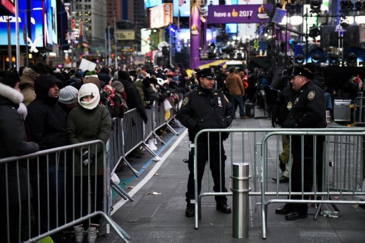 New York Police Department officers stand near barriers near where revelers wait for the beginning of New Year's Eve festivities in the Times Square area of New York, December 31, 2016. REUTERS/Mark Kauzlarich