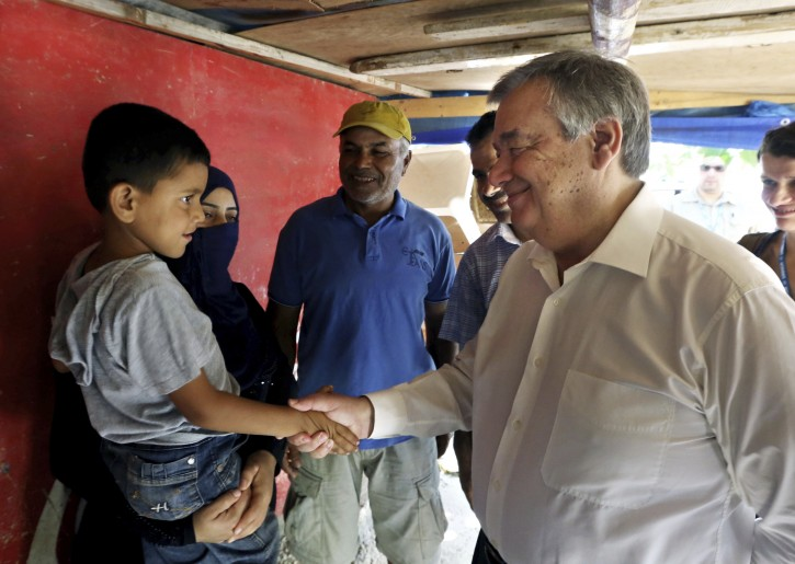 FILE- In this June 19, 2016 file photo, United Nations High Commissioner for Refugees Antonio Guterres shakes hands with a Syrian child during his visit to Khaldeh, south of Beirut, Lebanon. Guterres begins a five year term at the helm of the United Nations on January 1, 2017. (AP Photo/Bilal Hussein, File)