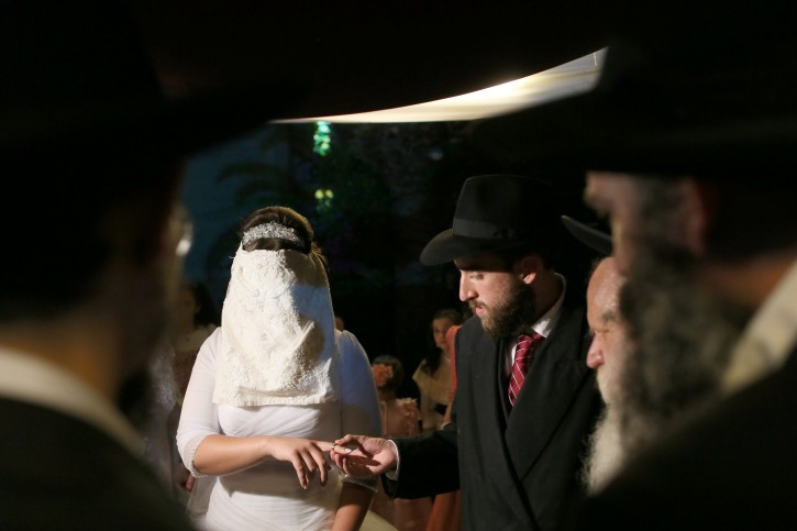 FILE - A groom places the ring on his bride's finger during a traditional Jewish wedding in  Kfar habad, Aug 26 2012. Photo by Nati Shohat/Flash90