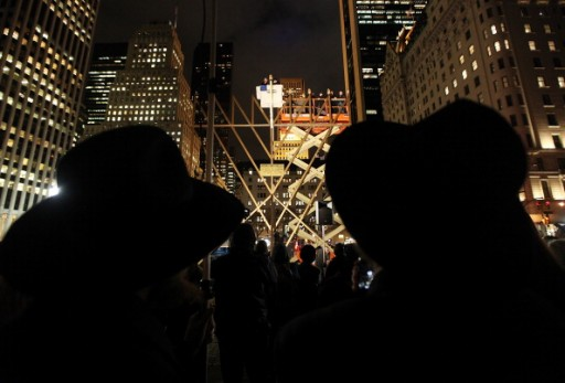 """FILE - Onlookers watch during the lighting of what is billed as the """"World's Largest Menorah"""" in Grand Army Plaza in Manhattan on December 11, 2012 in New York City.  (Photo by Mario Tama/Getty Images)"""