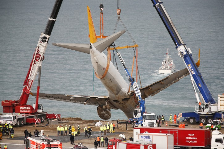 Cranes lift a Boeing 737-800 of Turkey's Pegasus Airlines in Trabzon, Turkey, Thursday, Jan. 18, 2018. Turkish authorities lifted the passenger plane that skidded off a runway in northern Turkey and stopped on the side of a slope meters away from the Black Sea, late Saturday. All passengers and crew were evacuated and no one was injured. (AP Photo/Lefteris Pitarakis)
