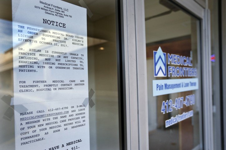 In this Dec. 21, 2017, photo, a notice stating the license to practice medicine for Dr. Andrzej Zielke has been suspended, is posted on the door at the closed Medical Frontiers office in Gibsonia, Pa. (AP Photo/Keith Srakocic)