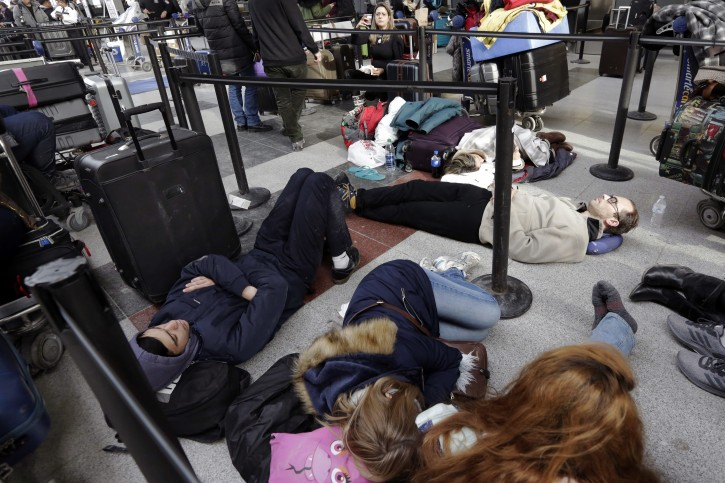 """Avianca passengers lay on the floor of New York's John F. Kennedy Airport Terminal 4, Monday, Jan. 8, 2018. The Port Authority of New York and New Jersey said Monday it will investigate the water pipe break that added to the weather-related delays at Kennedy Airport and will """"hold all responsible parties accountable."""" (AP Photo/Richard Drew)"""