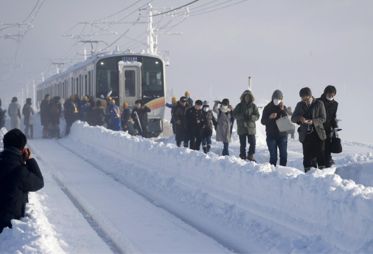 Passengers take shelter from a stranded train in Sanjo, Niigata prefecture, north of Tokyo Friday, Jan. 12, 2018. A Japanese railway official says about 430 people were stuck on the train overnight because of heavy snow that blanketed much of the country's Japan Sea coast. (Suo Takekuma/Kyodo News via AP)