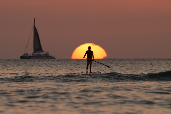 FILE - In this Tuesday, Dec. 31, 2013, file photo, a paddleboarder looks our over the Pacific Ocean as the sun sets off of Waikiki Beach, in Honolulu. When you're just starting out, credit card rewards offer some much-needed financial breathing room and opportunities to travel farther than you thought possible. (AP Photo/Carolyn Kaster, File)