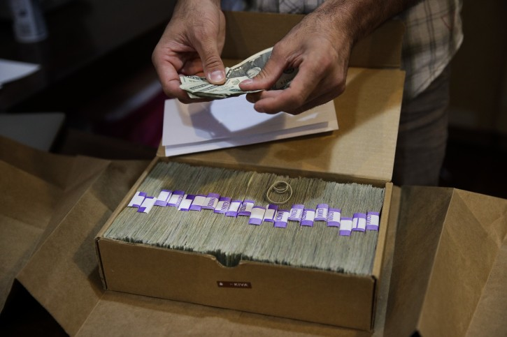 FILE - In this June 27, 2017, file photo, Jerred Kiloh, owner of the Higher Path medical marijuana dispensary, prepares his monthly tax payment, $40,131.88 in cash in Los Angeles. For Kiloh, the cash is a daily hassle. (AP Photo/Jae C. Hong, File)
