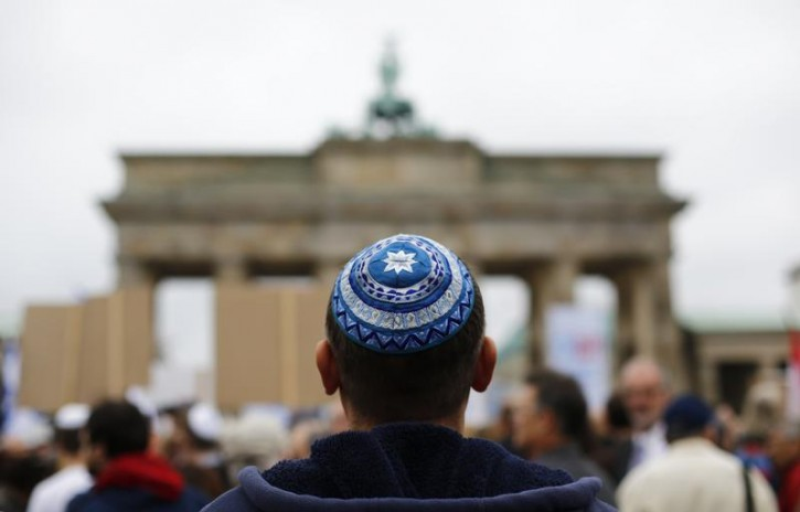 FILE - A man wearing a kippah waits for the start of an anti-Semitism demo at Berlin's Brandenburg Gate September 14, 2014. Placard reads ' Never again'.   REUTERS/Thomas Peter