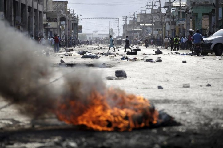FILE - Two women cross a street blocked by rocks and a burning barricade before a demonstration against the government in Port-au-Prince, Haiti, January 24, 2016. Reuters