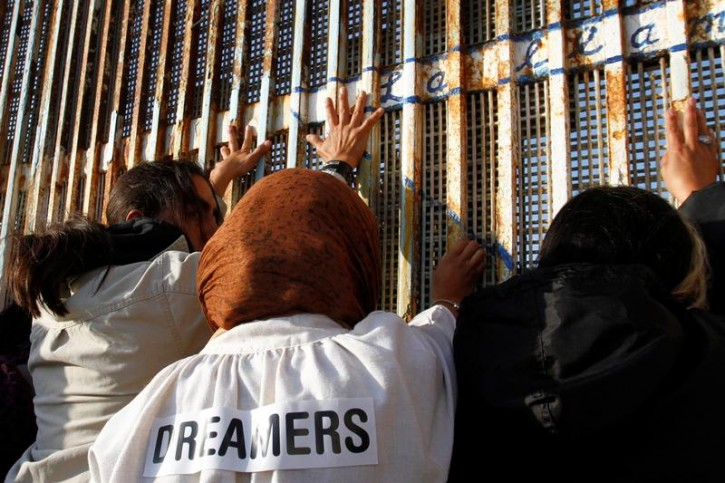 """""""Dreamers"""", undocumented immigrants who arrived in the U.S. when they were children, stand near the double steel fence that separates the U.S and Mexico at the border in Tijuana, Mexico, during the annual pre-Christmas """"Posada"""" celebration organised by immigrants and organisations from the U.S. and Mexico, December 16, 2017. REUTERS/ Jorge Duenes"""