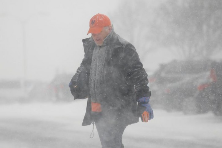A man crosses the street during a blizzard in Long Beach, New York, U.S. January 4, 2018. REUTERS/Shannon Stapleton