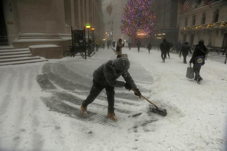 A man shovels snow along Wall Street during a snowstorm in New York City, New York, U.S., January 4, 2018. REUTERS/Lucas Jackson