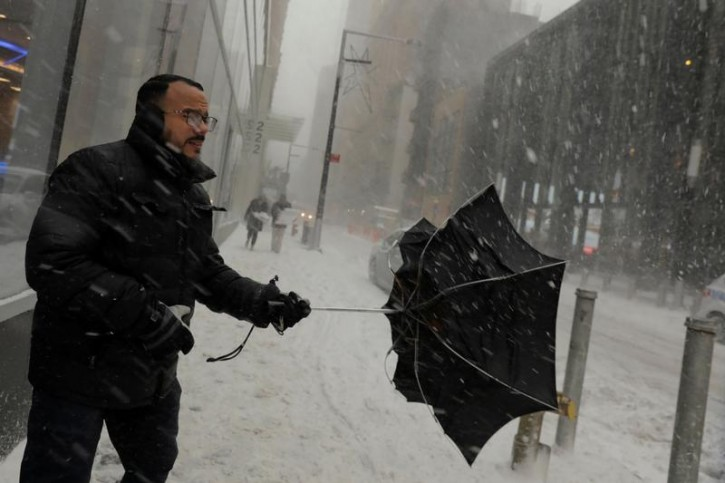A man holds onto his umbrella as the wind gusts during a snowstorm in New York, U.S., January 4, 2018.  REUTERS/Lucas Jackson
