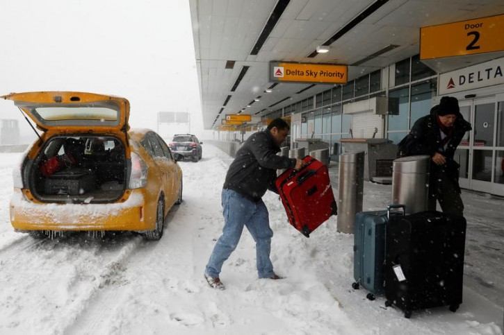 Travelers arrive at the Delta Airlines terminal at LaGuardia Airport during Storm Grayson in New York City, New York, U.S., January 4, 2018. REUTERS/Mike Segar