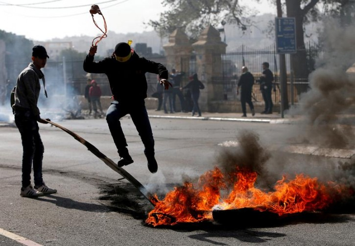 A Palestinian demonstrator jumps over a burning tire during clashes with Israeli troops, in the West Bank city of Bethlehem January 12, 2018. REUTERS/Mussa Qawasma