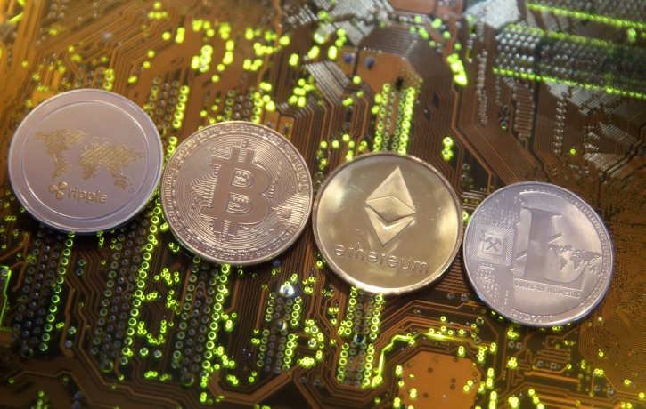Representations of the Ripple, Bitcoin, Etherum and Litecoin virtual currencies are seen on a PC motherboard in this illustration picture, February 13, 2018. Picture is taken February 13, 2018. REUTERS/Dado Ruvic/File Photo