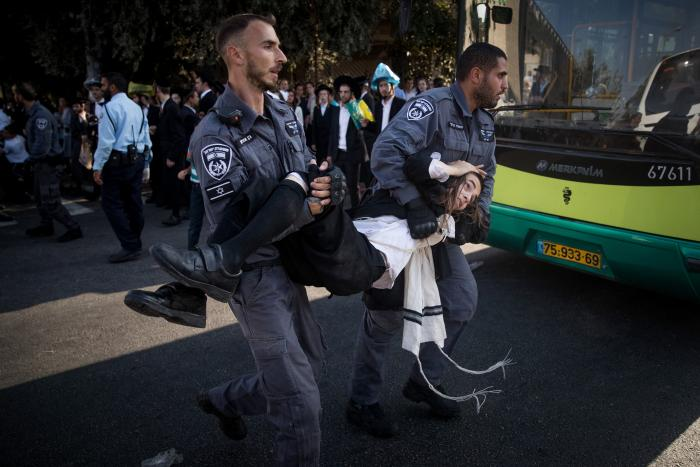 FILE - Ultra-Orthodox Jewish clash with Israeli police during a protest against the arrest of rabbi Shmuel Ya'akov Kahn grandson who failed to comply with a recruitment order, near the army recruiting office in Jerusalem, September 17, 2017. (Credit: Flash90)