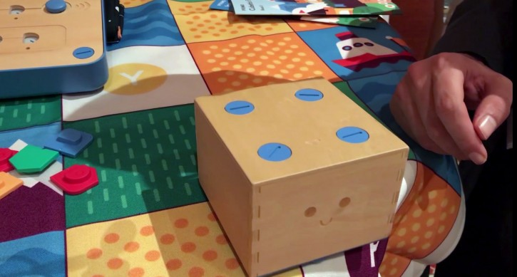 """In this Jan. 9, 2018, image made from a video, the Cubetto robot moves across a table following commands input into a board using blocks at the CES gadget show in Las Vegas. The 'Cubetto' block on wheels responds to where chip-embedded pieces are put on a wooden board. Different colors represent different commands, for example, to """"go straight"""" or """"turn left."""" (AP Photo/Ryan Nakashima)"""