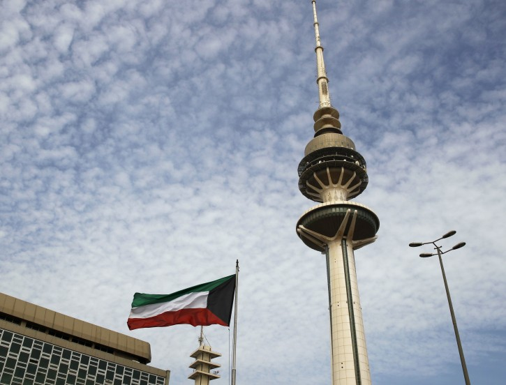 Kuwait's Liberation Tower is seen near a Kuwaiti flag in Kuwait City, Kuwait, Monday, Feb. 12, 2018. Kuwait this week is hosting a series of conferences on rebuilding Iraq after the onslaught of the Islamic State group. (AP Photo/Jon Gambrell)