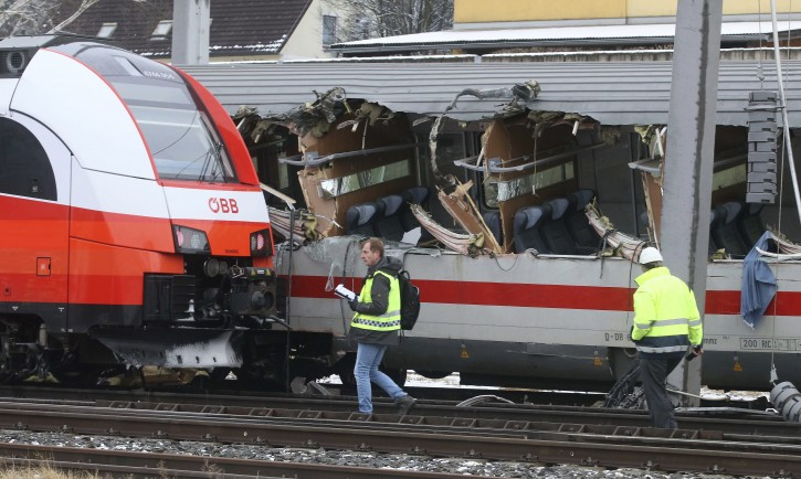 Rescue personnel and rail workers at the scene of a train crash in Niklasdorf, Austria, Monday, Feb. 12, 2018. Two passenger trains collided near a station of Niklasdorf. (AP Photo/Ronald Zak)