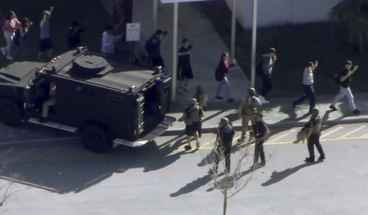 In this frame grab from video provided by WPLG-TV, students from the Marjory Stoneman Douglas High School in Parkland, Fla., evacuate the school following a shooting, Wednesday, Feb. 14, 2018. (WPLG-TV via AP)