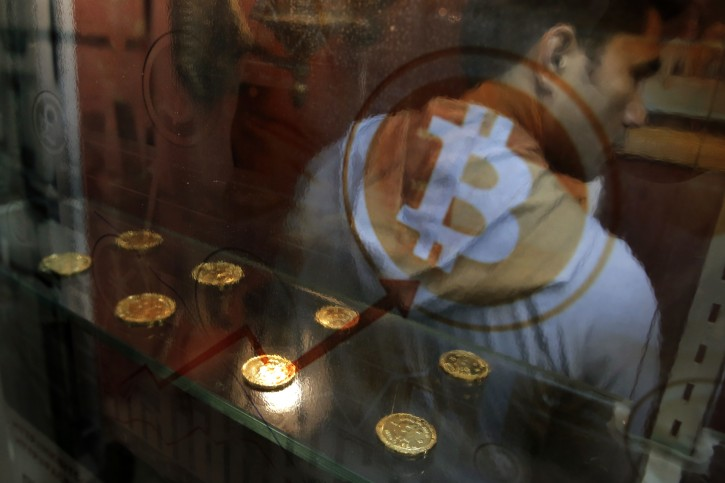 In this Friday, Dec. 8, 2017, file photo, a man uses a Bitcoin ATM in Hong Kong. Bitcoin is the world's most popular virtual currency. Such currencies are not tied to a bank or government and allow users to spend money anonymously. They are basically lines of computer code that are digitally signed each time they are traded. (AP Photo/Kin Cheung, File)