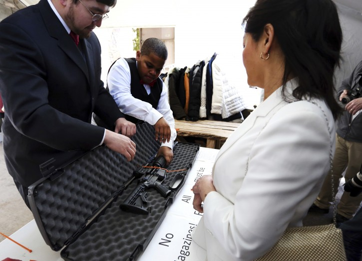 A woman has her weapon checked for being unloaded and zip-tied at the World Peace and Unification Sanctuary, Wednesday Feb. 28, 2018 in Newfoundland, Pa. Worshippers clutching AR-15 rifles participated in a commitment ceremony at the Pennsylvania-based church.The event Wednesday morning led a nearby school to cancel classes for the day. The church's leader, the Rev. Sean Moon, said in a prayer that God gave people the right to bear arms. (AP Photo/Jacqueline Larma)