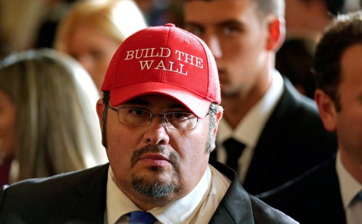 """FILE - Wearing a """"Build the Wall"""" hat, Fredy Burgos, a member of the Central Committee of the Virginia Republican Party, attends an event to commemorate Hispanic Heritage Month hosted by U.S. President Donald Trump at the White House in Washington, U.S., October 6, 2017.  REUTERS/Kevin Lamarque"""