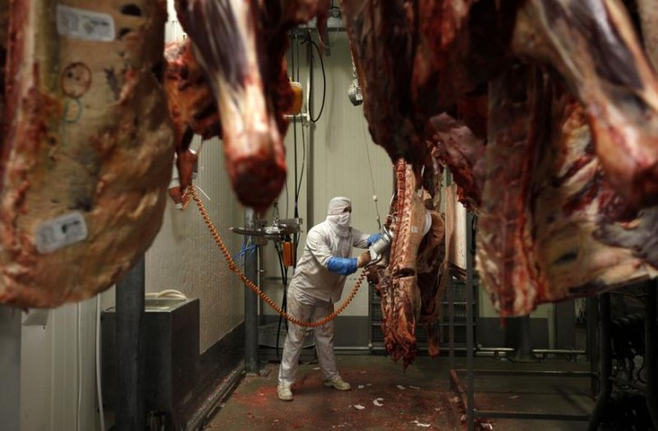 FILE - A worker cuts carcasses into pieces in the Biernacki Meat Plant slaughterhouse in Golina near Jarocin western Poland July 17, 2013. REUTERS