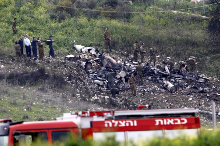 Israeli soldiers inspect the remains of an Israeli F-16 fighter jet that was shot down after a hit by Syrian anti-aircraft system, near the northern Israeli Kibbutz (collective community) of Harduf, 10 February 2018. EPA
