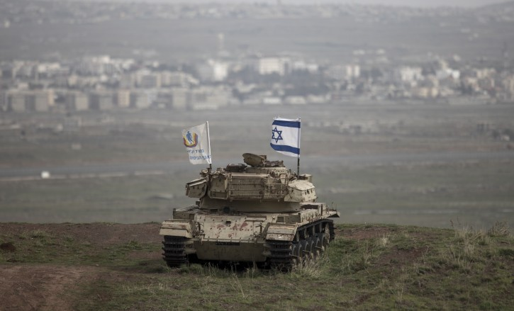 An Israeli flag is raised on an old Israeli tank from the remains of the Israeli-Syrian war in 1973 near the Syrian city of Quneitra (background) in the Golan Heights, 11 February 2018. EPA