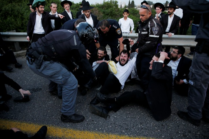 Israeli ultra-Orthodox Jewish men clash with police as they block a main road during a protest against the detention of a member of their community who refuses to serve in the Israeli army, in Bnei Brak, Israel, March 12, 2018. REUTERS/Ammar Awad