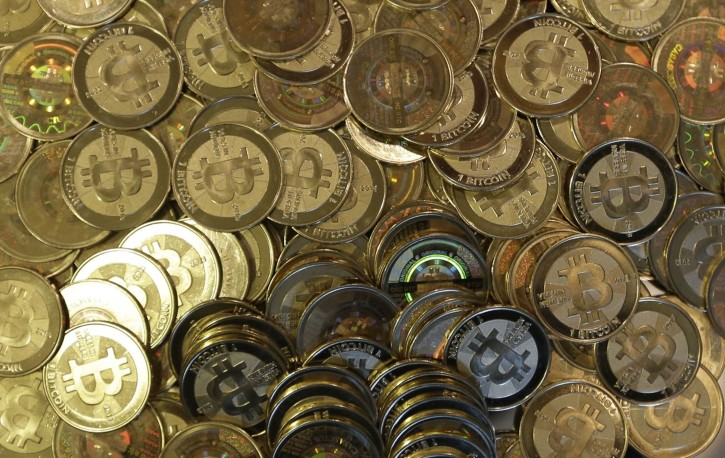 FILE - This April 3, 2013 file photo shows bitcoin tokens at a shop in Sandy, Utah. A new report warns central banks should carefully weigh the risks before introducing virtual currencies using the technology that enables bitcoin.(AP Photo/Rick Bowmer, file)