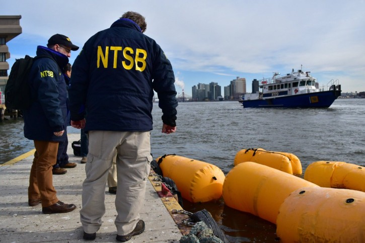 NTSB (National Transportation Safety Board) investigators arrive at the scene of the wreckage of a chartered Liberty Helicopters helicopter that crashed into the East River as it sits submerged under yellow flotation devices in New York, U.S., March 12, 2018