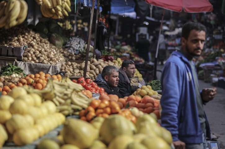 A Palestinian seller is seen next to his vegetables grocery in Gaza,on February 20, 2018.