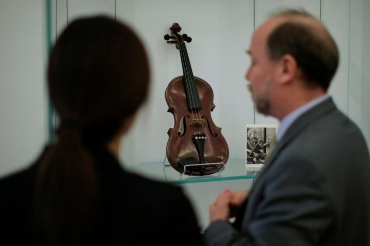 People take a look at Albert Einstein's violin which will be out for auction at Bonhams auction house in New York, U.S., March 6, 2018. REUTERS/Eduardo Munoz