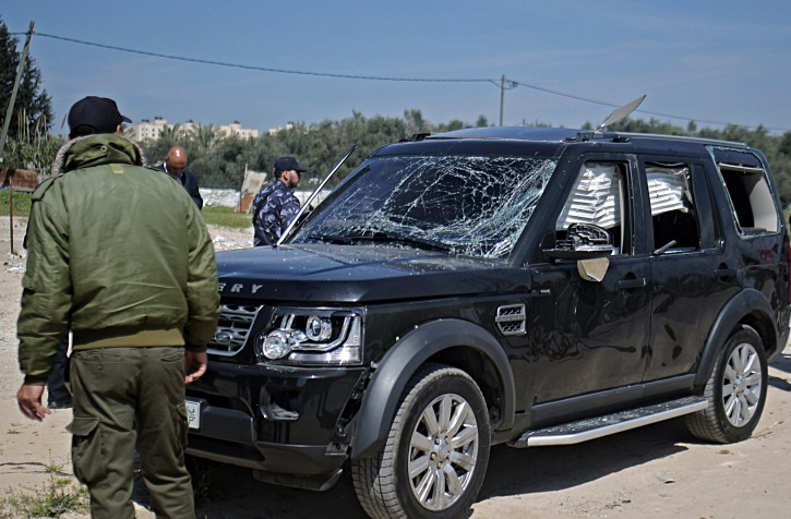 Hamas security officials inspect one of the cars of Palestinian Prime Minister Ramil Hamdallah's convoy that was targeted in an attack after his arrival in Beit Hanun town, the northern Gaza Strip, 13 March 2018. EPA