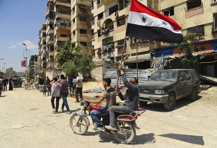 In this photo released on Saturday, April 14, 2018 by the Syrian official news agency SANA, shows Syrian men ride a motorcycle and waving their national flag, after Syrian police units entered the town of Douma, the site of a suspected chemical weapons attack and the last rebel-held town in the eastern Ghouta, near Damascus, Syria. AP