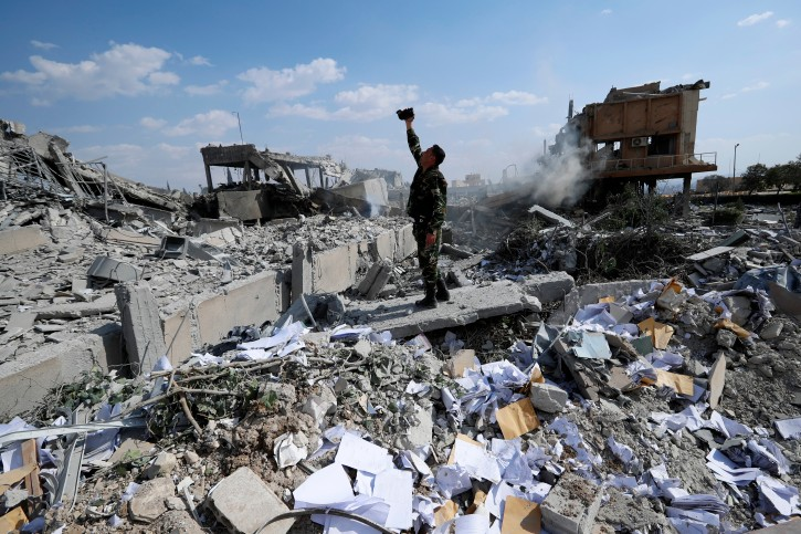 A Syrian soldier films the damage of the Syrian Scientific Research Center which was attacked by U.S., British and French military strikes to punish President Bashar Assad for suspected chemical attack against civilians, in Barzeh, near Damascus, Syria, Saturday, April 14, 2018.  (AP Photo/Hassan Ammar)
