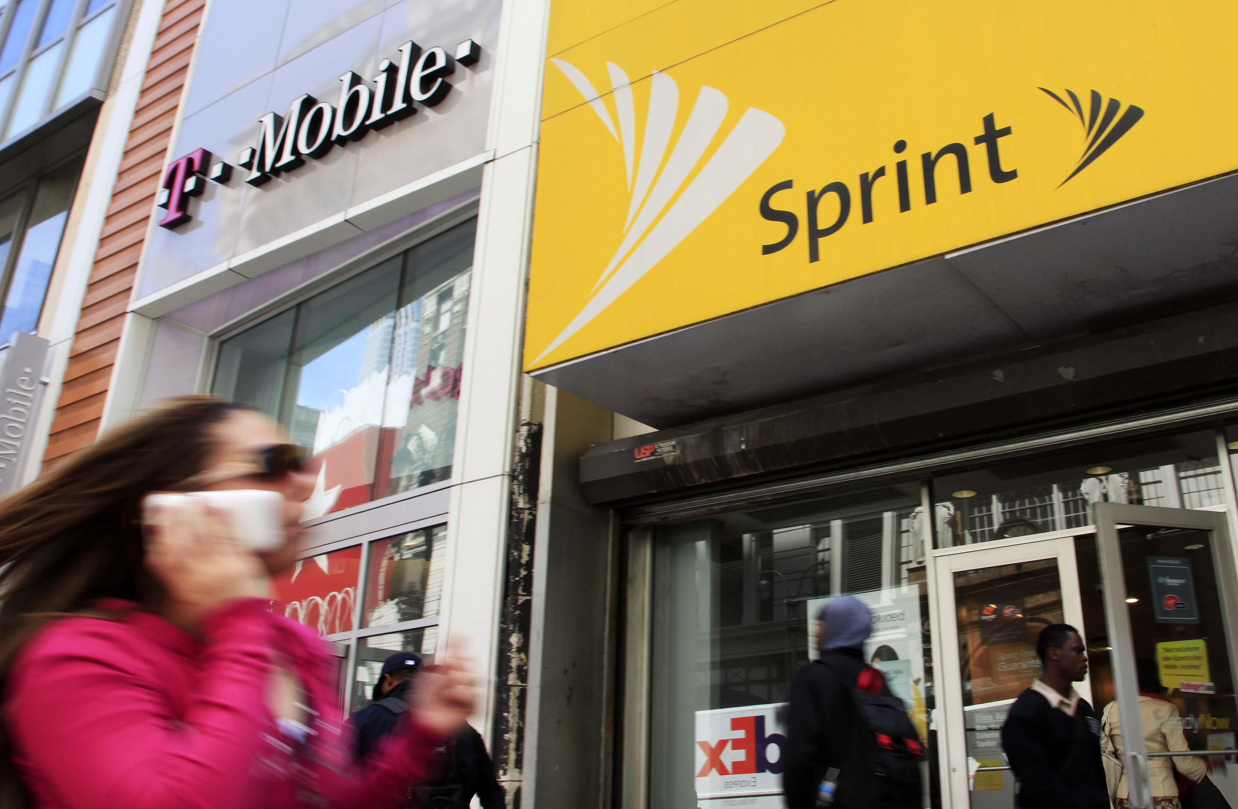 A woman using a cell phone walks past T-Mobile and Sprint stores, Tuesday, April 27, 2010, in New York. Sprint Nextel Corp. on Wednesday, April 28, said it lost a net 75,000 subscribers in the first three months of 2010, compared to a loss of 182,000 in the same quarter last year.(AP Photo/Mark Lennihan)