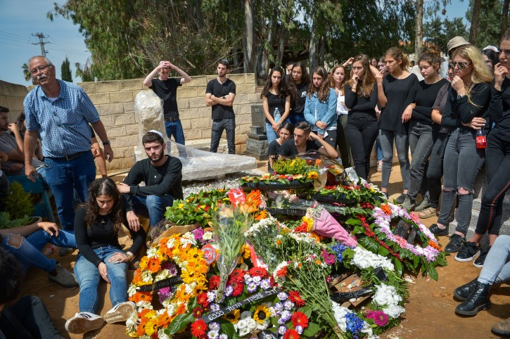 Friends of Tzur Alfi mourn near his grave during his funeral in Mazkeret Batya on April 27, 2018.Flash90