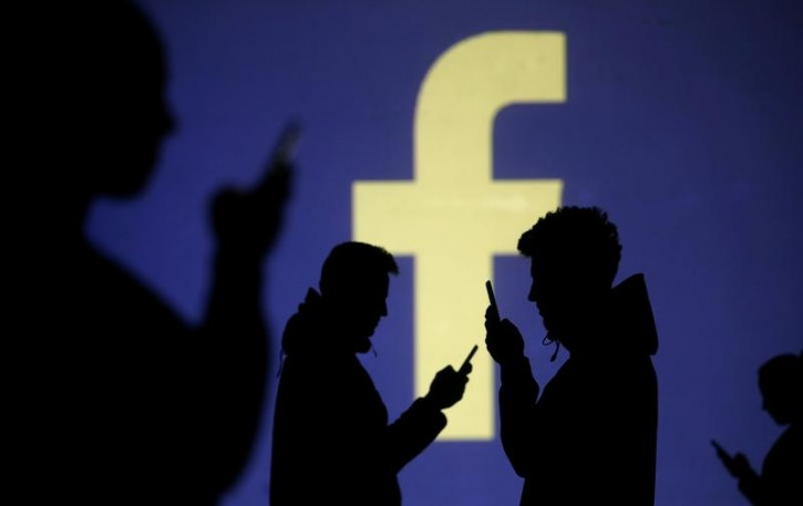 Silhouettes of mobile users are seen next to a screen projection of Facebook logo in this picture illustration taken March 28, 2018.  REUTERS/Dado