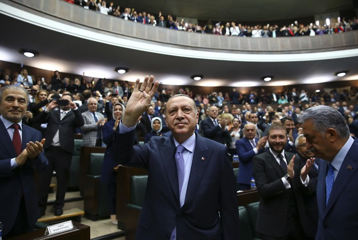 Turkey's President Recep Tayyip Erdogan waves to members of his ruling Justice and Development (AKP) Party, during its weekly meeting in Ankara, Turkey, Tuesday, May 8, 2018. Erdogan has reacted angrily to a group of some 300 well-known French personalities who urged prominent Muslims, by signing a manifesto which was published in Le Parisien newspaper on Sunday, to denounce anti-Jewish and anti-Christian references in the Quran, Islam's holy book. (Kayhan Ozer/Presidency Press Service via AP, Pool)