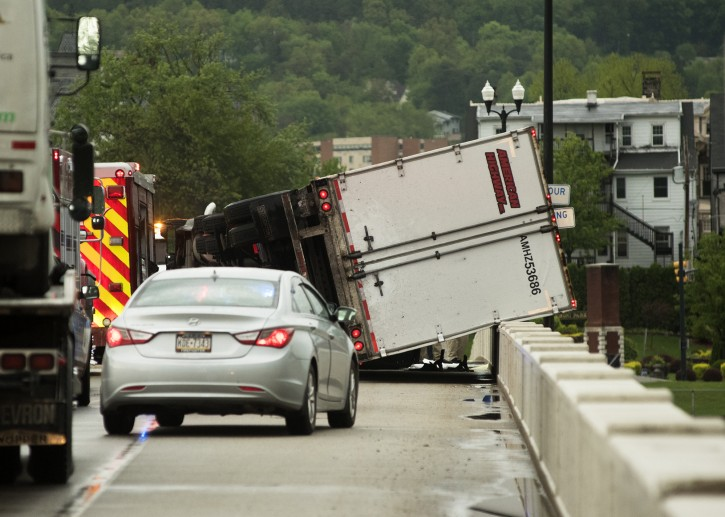 A Freightliner tractor-trailer, which was overturned by strong winds associated with a thunderstorm, rests on a barrier on a bridge crossing the Susquehanna River at Danville, Pa., on Tuesday, May 15, 2018. The driver, Mariusz Jarosz, of Des Plaines, Illinois, suffered a hand injury and was transported to a hospital. (AP PHOTO/The News-Item, Larry Deklinski)