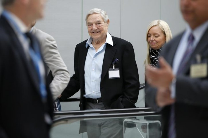 FILE - Georges Soros (C), Chairman of Soros Fund Management, arrives to attend the annual conference of the Institute for New Economic Thinking (INET) at the Organisation for Economic Cooperation and Development (OECD) headquarters in Paris April 9, 2015.   REUTERS/Charles Platiau