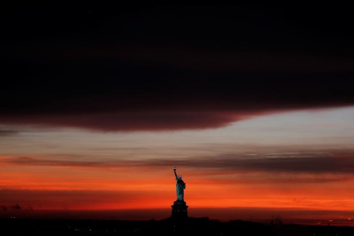 The sun sets behind the Statue of Liberty after a rain storm in New York, U.S., May 15, 2018.  REUTERS/Lucas Jackson