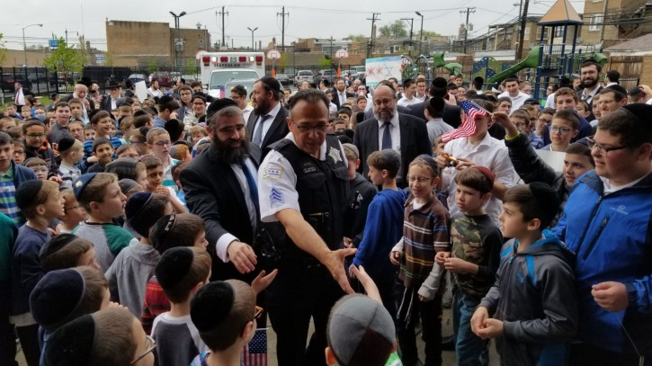 Police Sergeant Mark George greets young boys from Yeshiva Tiferes Tzvi in Chicago on May 14, 2018 (Courtesy)